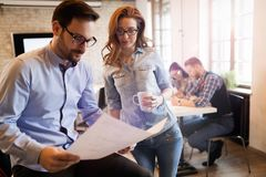 Young attractive architects discussing in modern office royalty free stock image