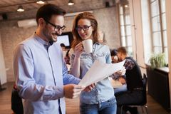 Young attractive architects discussing in modern office Stock Photography