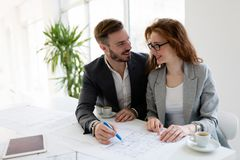Young attractive architects working on project in office. Young attractive architects working on project in their office Royalty Free Stock Image