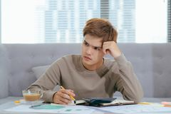 Young attractive Young Asian man at home sitting on sofa with ca. Lculator accounting costs, charges, taxes and mortgage for paying bills looking worried and Royalty Free Stock Images