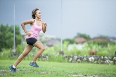 Young attractive Asian sport runner woman running in the jungle smiling happy in training workout on herb background in fitness. And healthy lifestyle concept Stock Photography