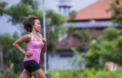 Young attractive Asian sport runner woman running in the jungle smiling happy in training workout on herb background in fitness. Young attractive Asian sport Stock Photo