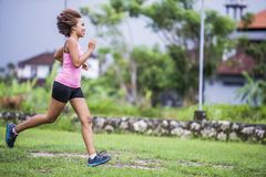 Young attractive Asian sport runner woman running in the jungle smiling happy in training workout on herb background in fitness. Young attractive Asian sport Stock Images