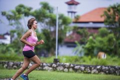Young attractive Asian sport runner woman running in the jungle smiling happy in training workout on herb background in fitness. Young attractive Asian sport Stock Photos