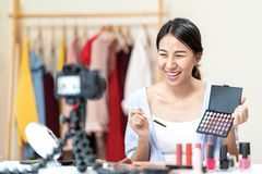 Free Young Attractive Asian Woman Beauty Blogger Or Vlogger Smiling Looking At Camera And Talking On Video Shooting While Make Up. Royalty Free Stock Image - 155903776