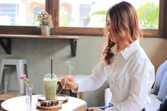 Young attractive Asian woman eating brownie dessert with fork in coffee cafe. Young attractive Asian woman eating brownie dessert with fork in coffee cafe Royalty Free Stock Photography