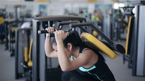 Young attractive asian woman in the gym. Footage by slider (dolly) right to left stock video
