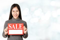 Young attractive asian woman holding sale signboard card showing for price tag looking at camera. In shopping super hot clearance mega sale concept feeling royalty free stock image