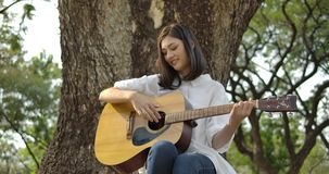 Young attractive asian woman playing acoustic guitar in a summer park. stock footage