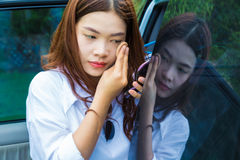 Young attractive asian woman, teen, putting make up on her face stock images
