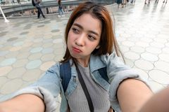 Young attractive Asian woman tourist taking a photo of selfie in urban city stock photography
