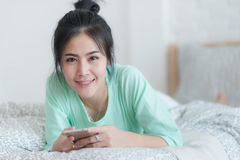 Young Asian woman stretching on bed after wake up. Young attractive Asian woman wear green casual cloths stretching after wake up on bed. Lazy girl activity on Royalty Free Stock Image