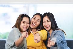 Young attractive asian women or three best friends sitting and pointing you looking at camera stock images