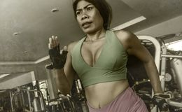Young attractive and athletic Asian Indonesian sport woman running on treadmill at gym fitness club training hard jogging workout. Focused and concentrated in stock images