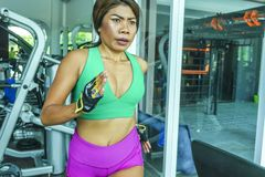 Young attractive and athletic Asian Indonesian sport woman running on treadmill at gym fitness club training hard jogging workout. Focused and concentrated in stock photography