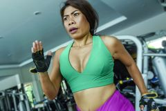 Young attractive and athletic Asian Indonesian sport woman running on treadmill at gym fitness club training hard jogging workout. Focused and concentrated in stock photos