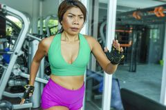 Young attractive and athletic Asian Indonesian sport woman running on treadmill at gym fitness club training hard jogging workout. Focused and concentrated in royalty free stock images