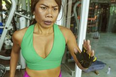 Young attractive and athletic Asian Indonesian sport woman running on treadmill at gym fitness club training hard jogging workout. Focused and concentrated in stock photo