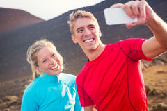 Young attractive athletic couple taking photo of themselves with Royalty Free Stock Photography