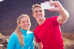 Young attractive athletic couple taking photo of themselves with Royalty Free Stock Images
