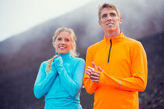 Young attractive athletic couple, wearing sporty cloths on trail Royalty Free Stock Image