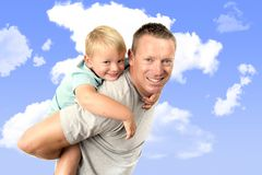 Young attractive and athletic father carrying on his back young beautiful and blond son having fun together posing isolated on blu Stock Image