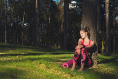 Young attractive athletic woman wearing smart watch is enjoying last rays of sun for the day after her workout. In a forest Stock Images