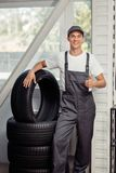 A young and attractive automechanic is standing near several car tires while at work stock image