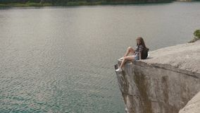 Young attractive backpacker girl relaxes by resting on mountain rock upon lake water surface below stock video