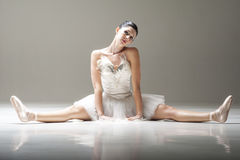 Young attractive ballerina sitting on the floor stretching her legs before a dance Royalty Free Stock Photos