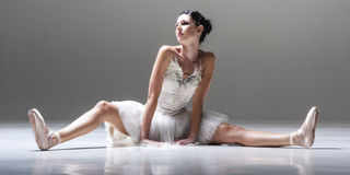 Young attractive ballerina sitting on the floor stretching her legs before a dance Stock Photo