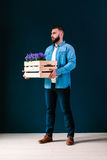 Young attractive bearded hipster man with brunette hair, dressed in blue denim shirt, stands indoors, holding wooden box Stock Photos