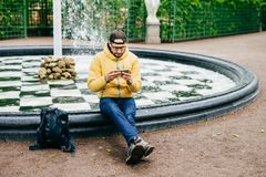 Young attractive bearded man in casual clothes sitting near stone fountain being concentrated into screen of his smartphone watchi royalty free stock image