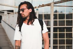 Attractive bearded man portrait with sunglasses. Young attractive bearded man with tattoos and long hair wearing sunglasses, white shirt and backpack posing on Stock Photo