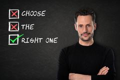 Young man with crossed arms and `Choose the right one` text on a blackboard background royalty free illustration