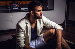 Young attractive bearded men in white suit pose in modern room. Young attractive bearded man in white suit pose in modern room. Photo stock photography