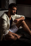 Young attractive bearded men in white suit pose in modern room. Young attractive bearded man in white suit pose in modern room. Photo royalty free stock photography