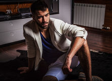 Young attractive bearded men in white suit pose in modern room. Young attractive bearded man in white suit pose in modern room. Photo stock images