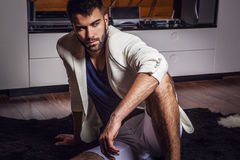 Young attractive bearded men in white suit pose in modern room. Young attractive bearded man in white suit pose in modern room. Photo stock photos