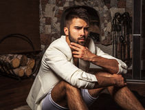 Young attractive bearded men in white suit pose in modern room. Stock Images