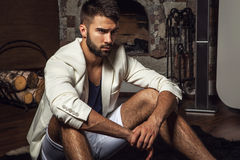 Young attractive bearded men in white suit pose in modern room. Stock Photography