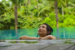 Young attractive and beautiful Asian Korean woman relaxing happy at tropical beach resort swimming at jungle infinity pool stock images