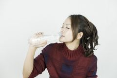 Young attractive beautiful asian woman drinking water from plastic bottle. royalty free stock images