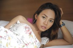 Young attractive and beautiful Asian woman lying on bed at bedroom posing sexy in beauty indoors studio set. Portrait of young attractive and beautiful Asian Stock Image