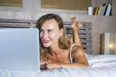 Young attractive and beautiful happy Caucasian woman 30s lying in bed at home using internet working on computer laptop smiling re. Laxed and cheerful at her royalty free stock photos