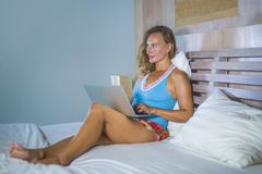 Young attractive and beautiful happy Caucasian woman 30s lying in bed at home using internet working on computer laptop smiling re. Laxed and cheerful at her stock image