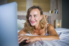 Young attractive and beautiful happy Caucasian woman 30s lying in bed at home using internet working on computer laptop smiling re. Laxed and cheerful at her stock images