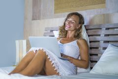 Young attractive and beautiful happy Caucasian woman 30s lying in bed at home using internet working on computer laptop smiling re. Laxed and cheerful at her royalty free stock image