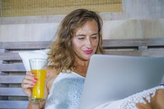 Young attractive beautiful happy woman 30s in bed at home using internet working on computer laptop smiling relaxed drinking orang. Young attractive and royalty free stock images