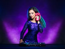 Young, beautiful and dj girl playing music on a disco party in a night club. Young, attractive and beautiful and dj girl playing music on a disco party in a royalty free stock photos